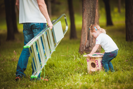 animal  bird: Happy father making Wooden birdhouse with daughter in summer green park Stock Photo