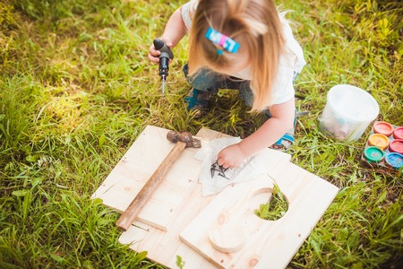 making fun: Little girl making Wooden birdhouse in summer green park