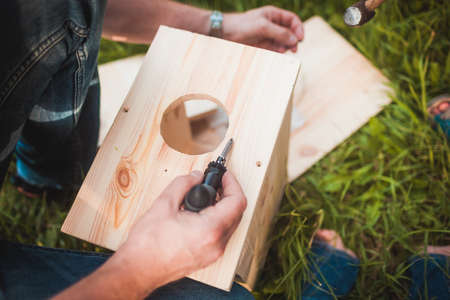 making up: Male hands making wooden birdhouse in green park close up Stock Photo