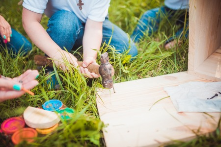 making hole: Happy family making Wooden birdhouse with hammer in summer green park close up