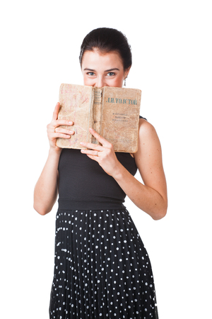 schoolmaster: Pretty girl in elegant dress standing is hiding her face with the opened book , isolated on white background