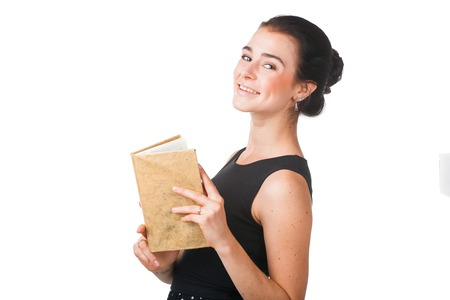schoolmaster: Smiling pretty girl in elegant dress standing with the opened book, isolated on white background Stock Photo