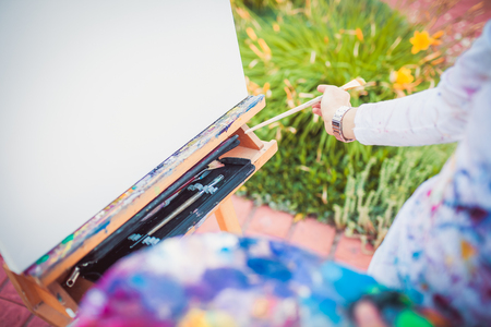 Female hand with paintbrush and easel