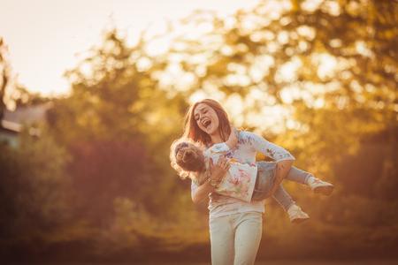 niños felices: Madre y pequeña hija jugando juntos en un parque Foto de archivo