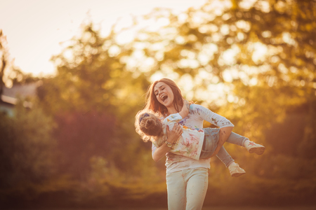 ni�os riendose: Mother and little daughter playing together in a park