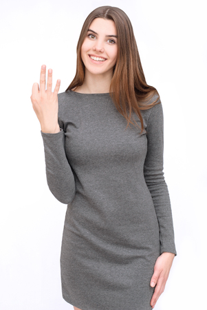 fingers: portrait of happy woman in grey dress showing three fingers
