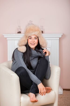 flaps: Beautiful girl in white fur hat hat with ear flaps are sitting in armchair near fireplace