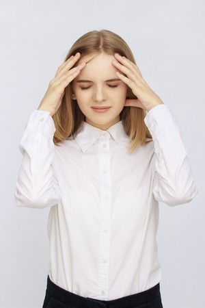 Young businesswoman suffering from headache on isolated background