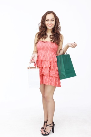 pink posing: Happy young woman posing in pink dress with shopping bags isolated on white background Stock Photo