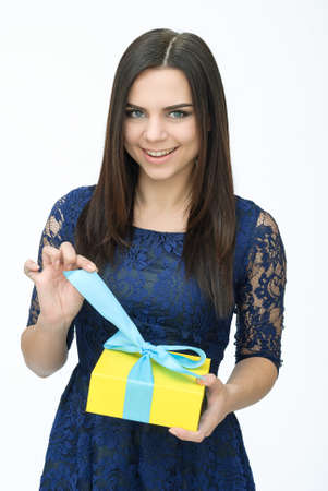 opening gift: Present. woman in blue dress opening gift