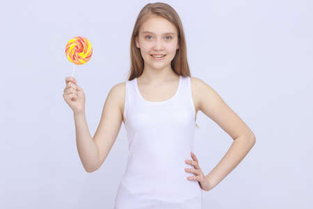 Young excited woman holding lolipop on isolated background