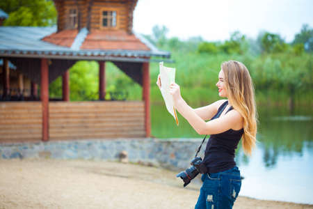 Young woman traveling in country by weekend. searching road on the map. looking place for photo Stock Photo