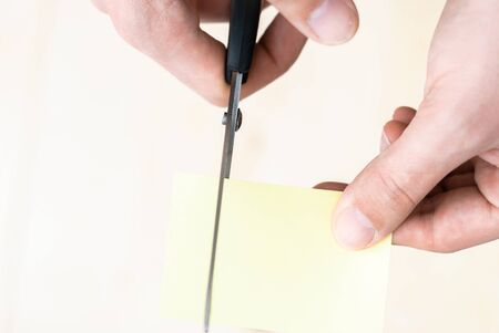 A man is cutting a sheet of yellow paper using metallic scissors