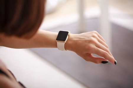 timepiece: using her smartwatch at home in the living room