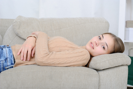 home comforts: Closeup of a smiling young woman lying on couch Stock Photo