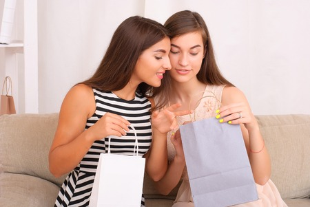 Happy women together looking purchases from shopping bags at home