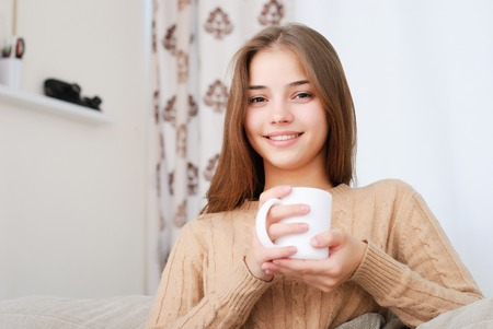 potěšen: Portrait of young brunette woman sitting on couch in her living room and drinking coffee or tea.