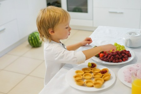 boy preparing breakfast in white kitchen. Healthy food for children Stock Photo