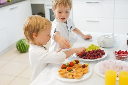 Two boys preparing breakfast in white kitchen. Healthy food for children