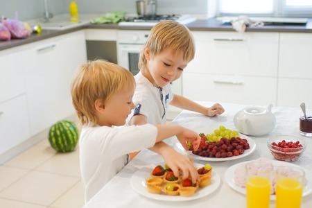 raspberry dress: Two boys preparing breakfast in white kitchen. Healthy food for children