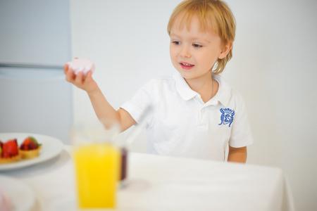 raspberry dress: boy preparing breakfast in white kitchen. Healthy food for children Stock Photo