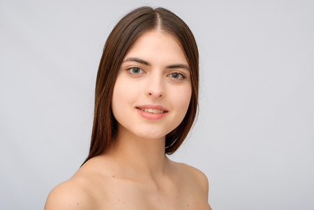 Portrait of beautiful young woman with clean skin on grey background