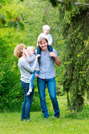 family life: Happy young family spending time together outside in green park Stock Photo
