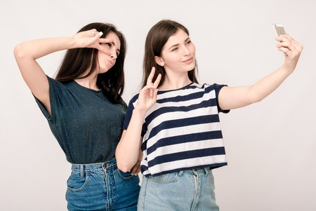 grimaces: Positive friends portrait of two happy sister girls making selfie, funny faces, grimaces, joy, emotions, casual style on light grey background Stock Photo
