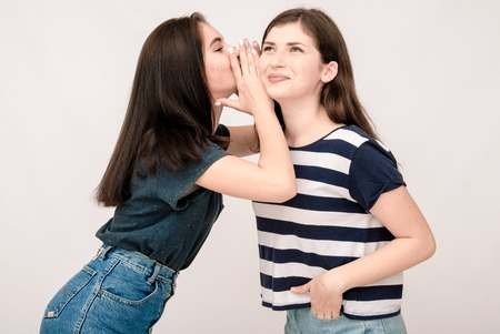 grimaces: Portrait of a two girls gossip on gray background. Funny faces, grimaces, joy, emotions, casual style