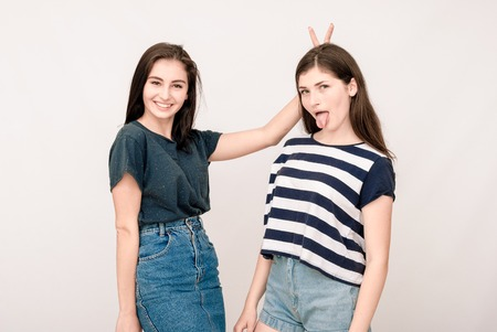 grimaces: Positive friends portrait of two happy sister girls, funny faces, grimaces, joy, emotions, casual style on light grey background