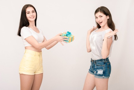 grimaces: Positive friends portrait of two happy girls with present, funny faces, grimaces, joy, emotions, casual style on light grey background