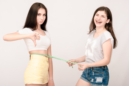 measure waist: Positive young girl making measure waist of her friends. Funny faces