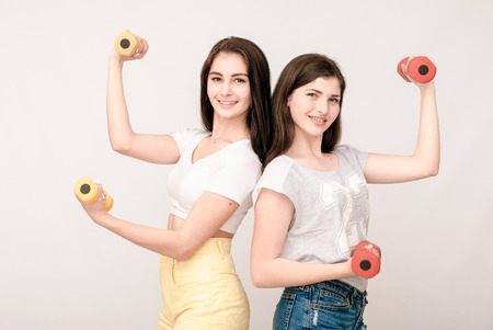 grimaces: Positive friends portrait of two happy sister girls with dumbbell, funny faces, grimaces, joy, emotions, casual style on light grey background
