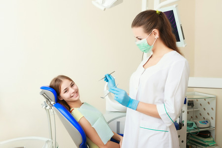a lady doctor: attractive woman dentist with girl patient in her office Stock Photo