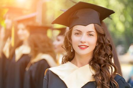 Graduate Studenten Graduierung Hut und Kleid trägt, im Freien Standard-Bild