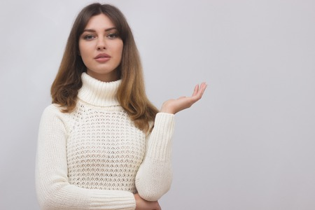 Woman in white sweater showing something with open hand palm. Caucasian female girl presenting something isolated on light grey background. Copyspase for product or sign text