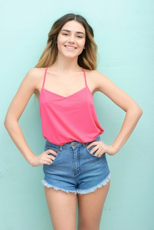 Young girl with long curly hair posing on blue background in studio. She wears shorts, pink T-shirt, pink sunglasses. She keeps hat overhead, holds blue skateboard on booty, looks excited.