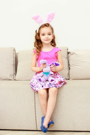 Cute little girl with bunny ears and cuddly toy sitting on sofa at home
