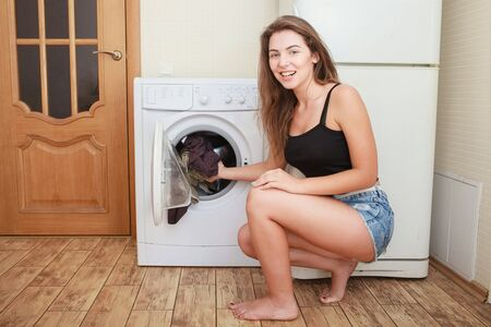 Housework: young woman doing laundry, shallow, color toned image