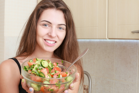 bawl: Portrait of a girl looking positive and holding a bawl with salad.