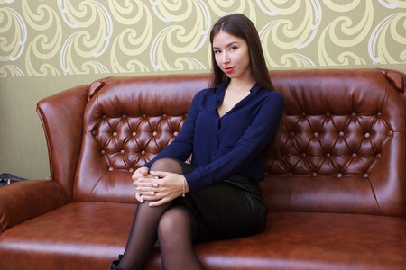 Beautiful girl with long legs in blue sits on red leather sofa