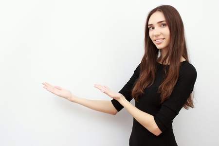 excited young woman presenting copy space on her palm Stock Photo