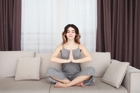 sooth: Young woman sitting on a sofa in the lotus position meditating Stock Photo