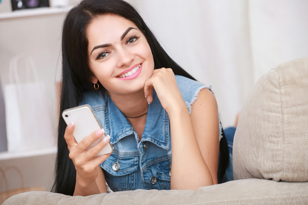 uses: Positive young woman lying on the couch and uses a mobile phone