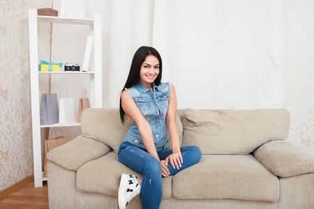 domicile: Relaxed casual brunette in blue cardigan and In blue jeans sits on the couch Stock Photo