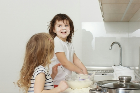 twin house: Mother with her 5 years old kids cooking holiday pie in the kitchen