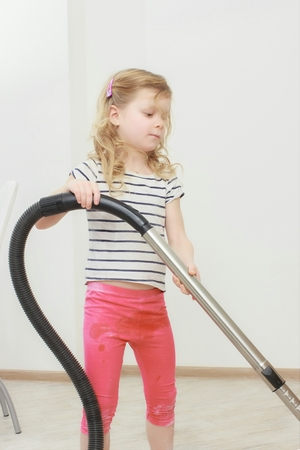 carpet clean: Little beautiful smiling girl running with vacuum cleaner Stock Photo