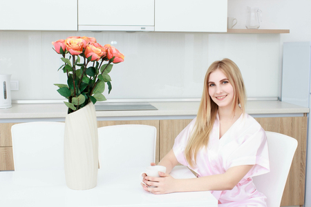 Young woman in pajamas sitting on chair with white cup and smiling