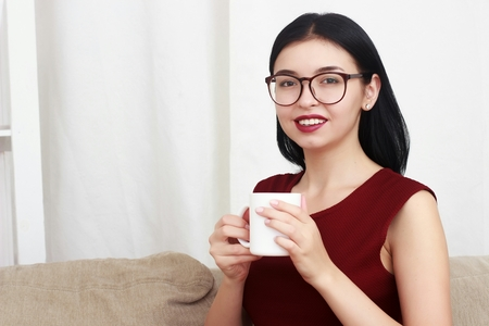 divan: Beautiful girl in red sweater sitting on couch posing and smiling with cup