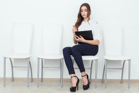 overworked: The girl sits on a chair and fills up the documents